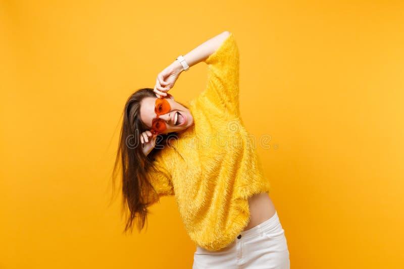 Ritratto della giovane donna felice allegra emozionante in pantaloni bianchi del maglione della pelliccia che giudicano i vetri a fotografie stock libere da diritti