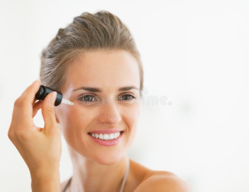 Ritratto della giovane donna felice che applica siero cosmetico immagine stock