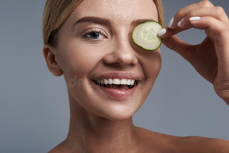 Ritratto della giovane donna felice che sorride e che tiene pezzo di cetriolo immagine stock