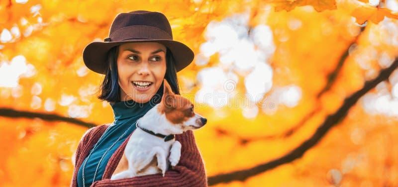Ritratto della giovane donna felice con il cane all'aperto in autunno fotografia stock