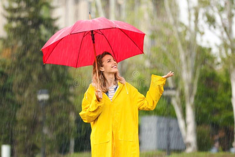 Ritratto della giovane donna felice con l'ombrello rosso in parco fotografia stock
