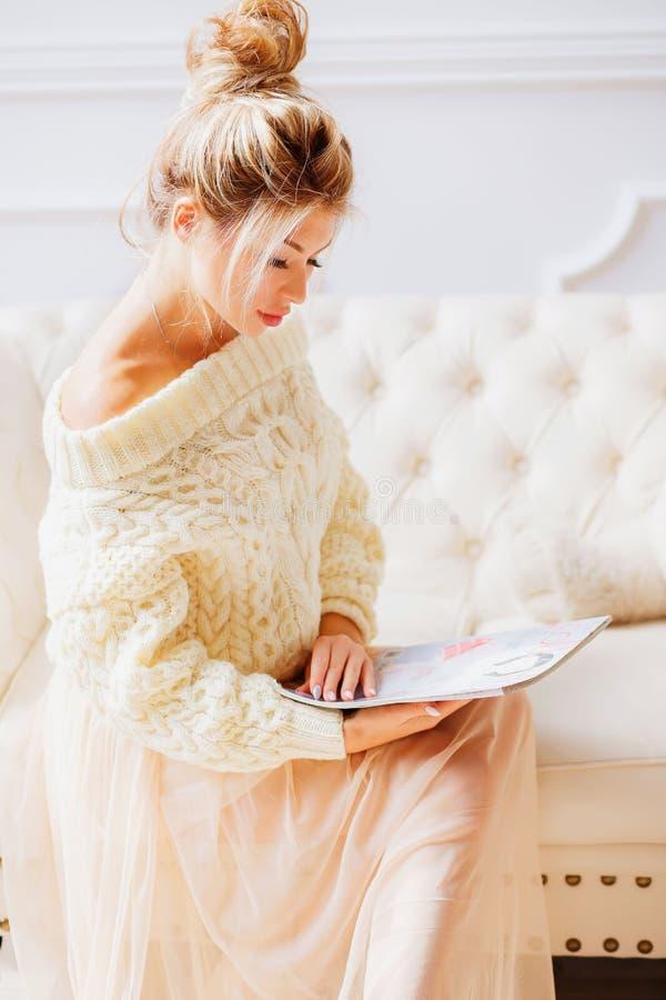 Ritratto della giovane donna felice con la rivista che si siede sullo strato a casa Ragazza bionda in un maglione su un interno d fotografia stock