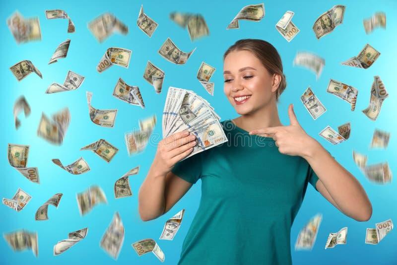 Ritratto della giovane donna felice con soldi sul fondo di colore fotografia stock libera da diritti