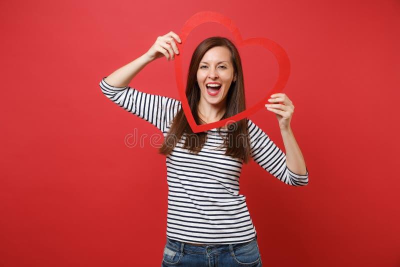 Ritratto della giovane donna graziosa allegra in vestiti a strisce casuali che giudicano grande cuore di legno rosso isolato su r fotografia stock libera da diritti