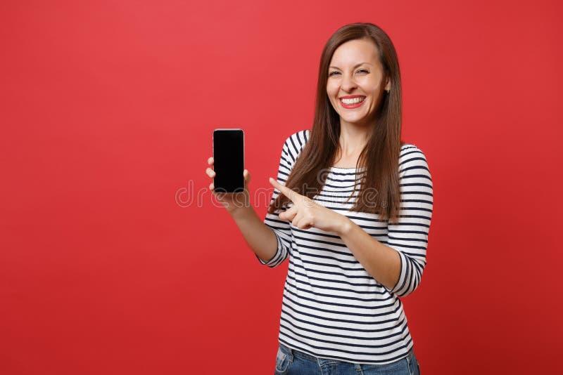 Ritratto della giovane donna graziosa che indica il dito indice sul telefono cellulare con lo schermo vuoto nero dello spazio in  fotografie stock