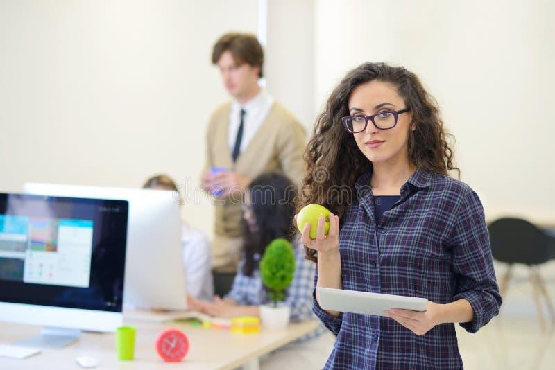 Ritratto della giovane donna graziosa che mangia una mela e che tiene compressa nel suo ufficio fotografie stock