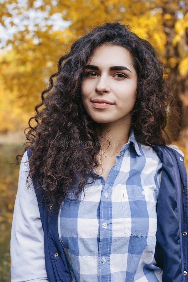 Ritratto della giovane donna graziosa con capelli ricci lunghi fotografia stock libera da diritti