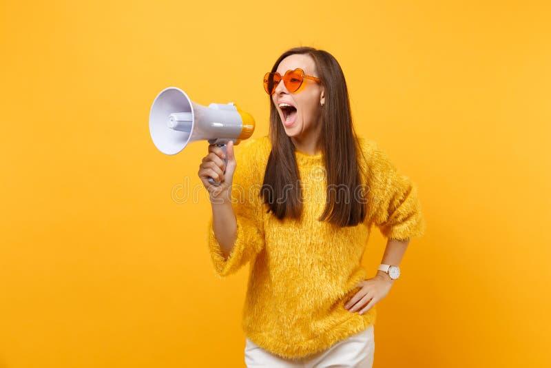 Ritratto della giovane donna graziosa divertente in maglione della pelliccia, occhiali arancio del cuore gridante sul megafono is fotografia stock