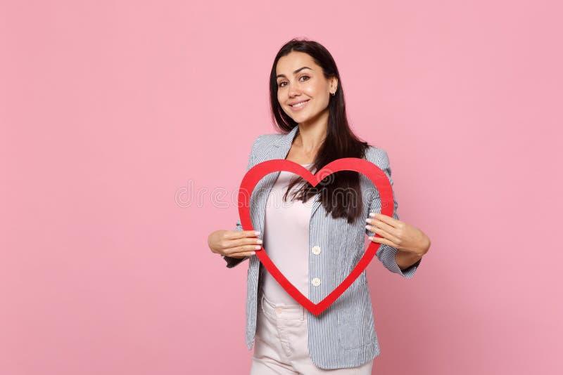 Ritratto della giovane donna graziosa sorridente in rivestimento a strisce che giudica grande cuore di legno rosso isolato sulla  fotografia stock libera da diritti