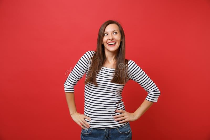 Ritratto della giovane donna graziosa vaga in vestiti a strisce che cerca, stante con akimbo di armi isolata su rosso luminoso fotografia stock libera da diritti