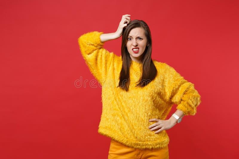 Ritratto della giovane donna imbarazzata interessata in maglione giallo della pelliccia che mette mano sulla testa isolata sulla  fotografia stock libera da diritti