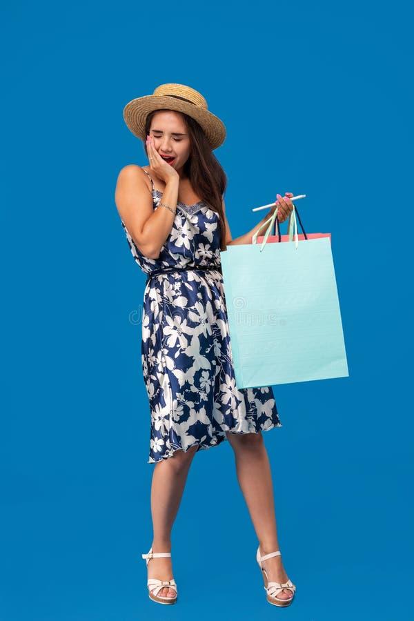 Ritratto della giovane donna infelice che guarda in suo portafoglio nel centro commerciale, speso troppo, non abbastanza contanti immagine stock