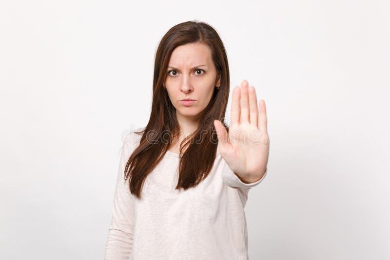 Ritratto della giovane donna interessata seria in vestiti leggeri che mostrano gesto di arresto con la palma isolata sulla parete fotografia stock libera da diritti