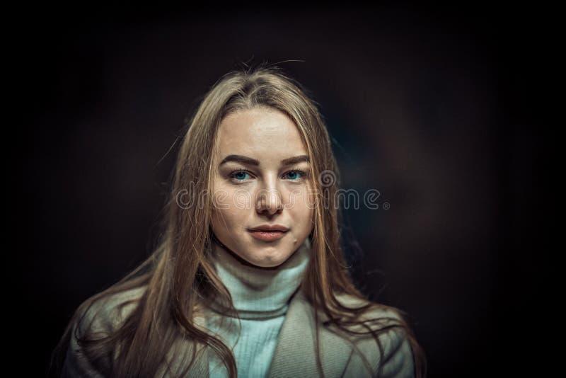 Ritratto della giovane donna nel sottopassaggio che aspetta il treno Guardando nella macchina fotografica Il buio pubblica fotografia stock