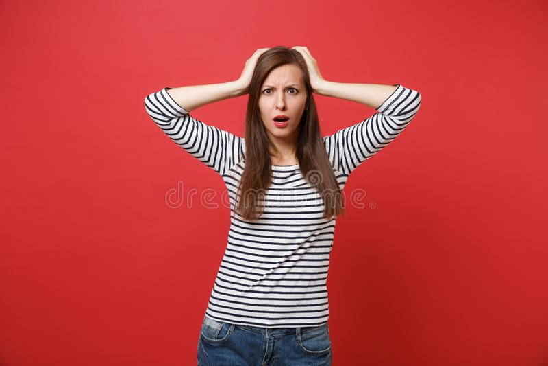 Ritratto della giovane donna perplessa colpita in vestiti a strisce che stanno e che mettono le mani sulla testa isolata su rosso fotografia stock libera da diritti