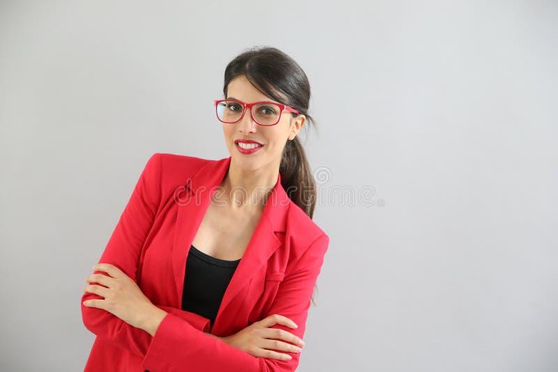 Ritratto della giovane donna in rivestimento rosso ed occhiali rossi fotografia stock