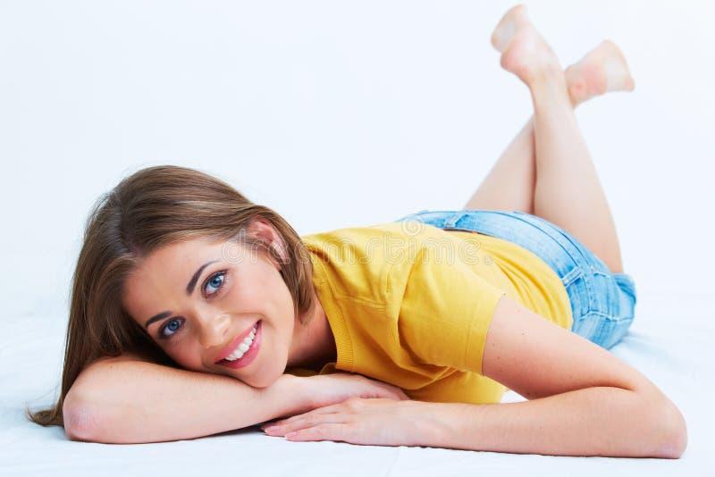 Ritratto della giovane donna sorridente che si trova sul pavimento fotografia stock