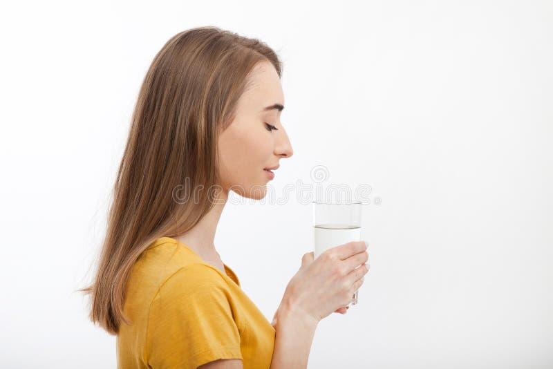 Ritratto della giovane donna sorridente che sta nel profilo e che tiene un bicchiere d'acqua Priorità bassa bianca Derisione su immagine stock
