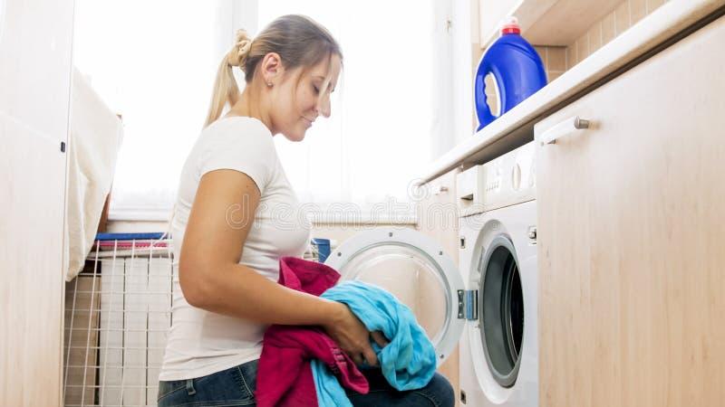 Ritratto della giovane donna sorridente con il mucchio dei vestiti in lavanderia fotografia stock