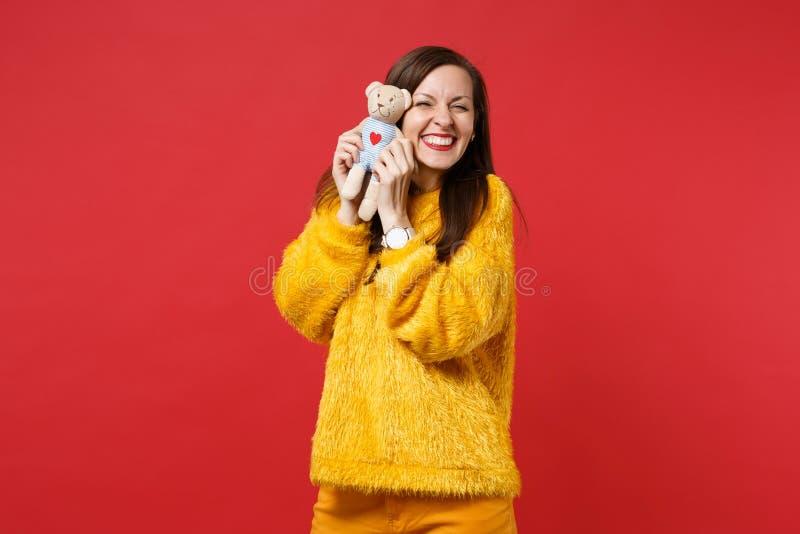 Ritratto della giovane donna sorridente graziosa in giocattolo giallo della peluche dell'orsacchiotto della tenuta del maglione d immagine stock libera da diritti
