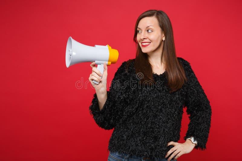 Ritratto della giovane donna sorridente in maglione nero della pelliccia che guarda da parte, giudicante megafono isolato sulla p fotografia stock libera da diritti