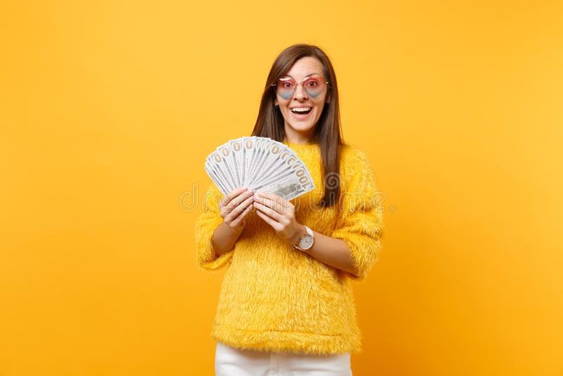 Ritratto della giovane donna sorridente in occhiali del cuore che tengono i lotti del pacco dei dollari, denaro contante isolato  immagine stock libera da diritti