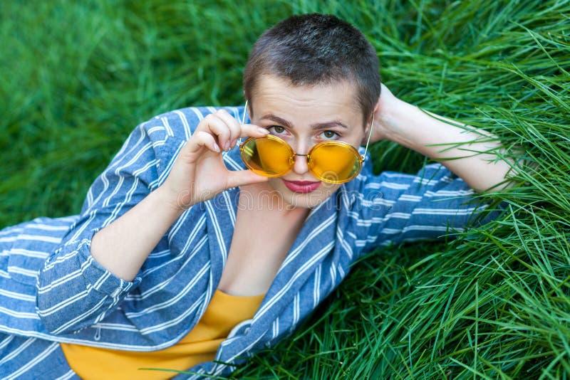 Ritratto della giovane donna sveglia seria con i capelli di scarsità in vestito a strisce blu casuale, camicia gialla ed occhial fotografia stock libera da diritti
