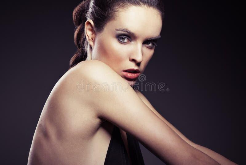Ritratto della giovane donna in vestito con la parte posteriore nuda fotografia stock