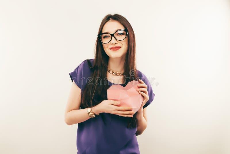 Ritratto della giovane donna in vetri con un cuore in sue mani Amore immagine stock libera da diritti