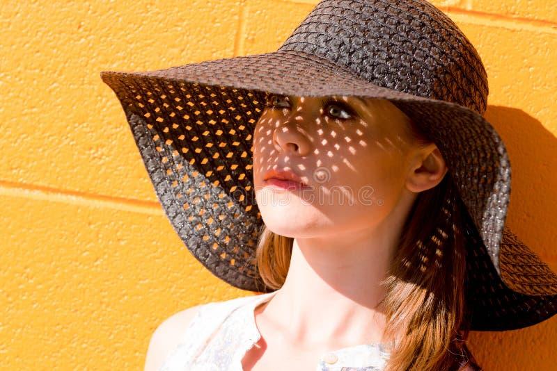 Ritratto della giovane signora attraente che porta il cappello di paglia nero immagine stock libera da diritti