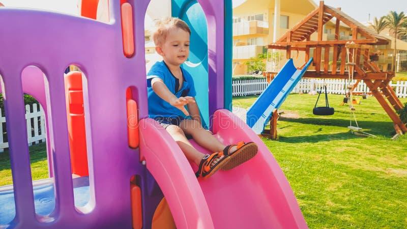 Ritratto della guida sorridente felice del ragazzo del bambino sullo scorrevole di plastica variopinto sul campo da giuoco dei ba fotografie stock