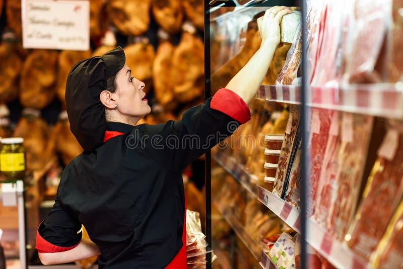 Ritratto della lavoratrice che prende i prodotti in di macelleria immagini stock