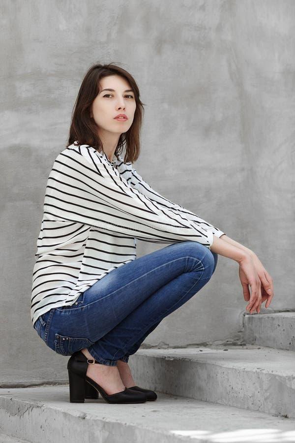 Ritratto della luce naturale all'aperto del modello di pratica della giovane donna castana alla moda che posa all'aperto contro i fotografie stock