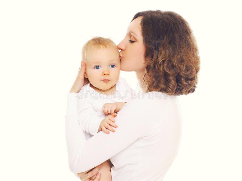 Ritratto della madre amorosa felice che bacia il suo bambino su un bianco fotografie stock libere da diritti