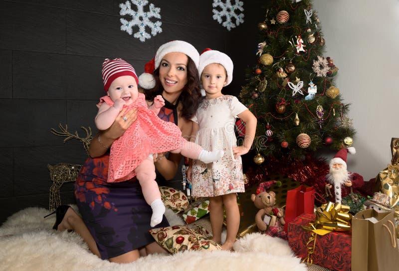 Ritratto della madre con due figlie in regolazioni di Natale fotografia stock