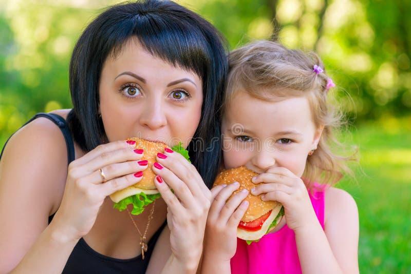 Ritratto della madre con sua figlia con gli hamburger immagine stock