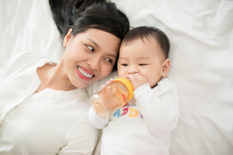 Ritratto della madre e del bambino asiatici felici divertendosi insieme a casa nella stanza bianca fotografie stock libere da diritti