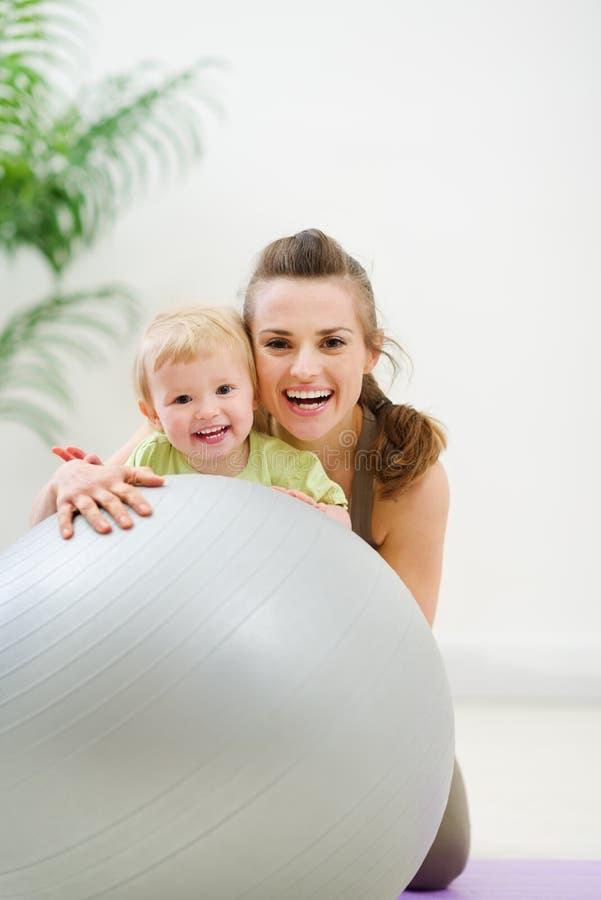 Ritratto della madre e del bambino sorridenti dietro la sfera fotografia stock libera da diritti