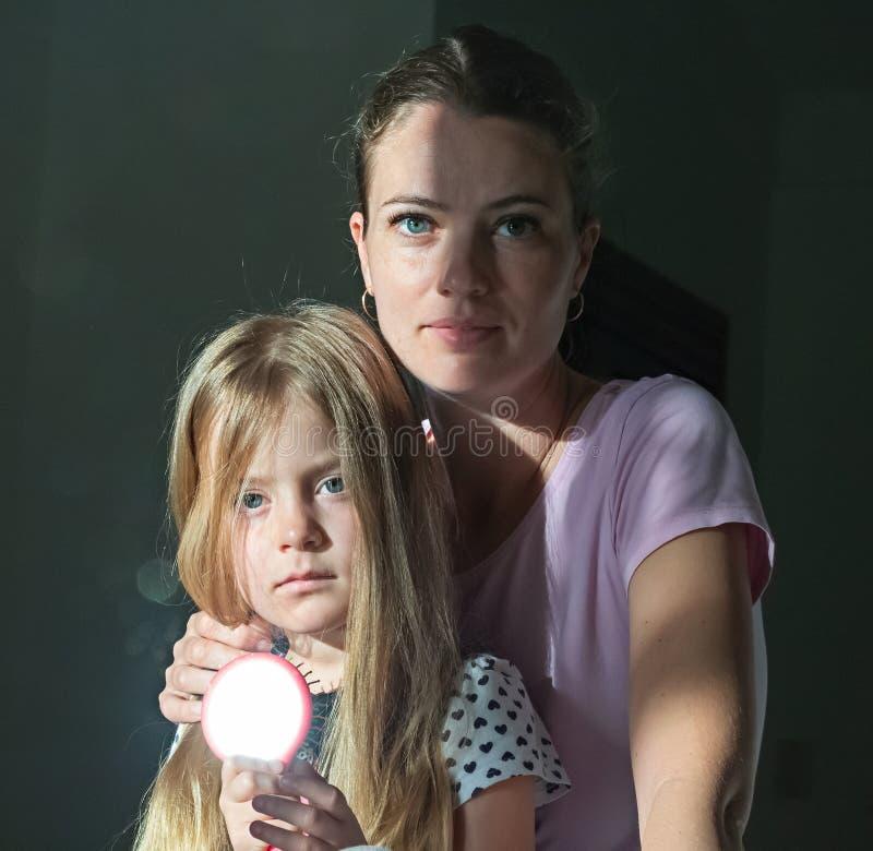Ritratto della madre e della figlia Bambina con uno specchio, facente Sunny Bunny Fondo scuro fotografia stock