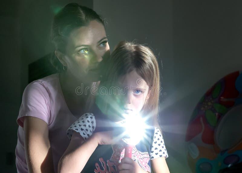 Ritratto della madre e della figlia Bambina con uno specchio, facente Sunny Bunny Fondo scuro immagine stock