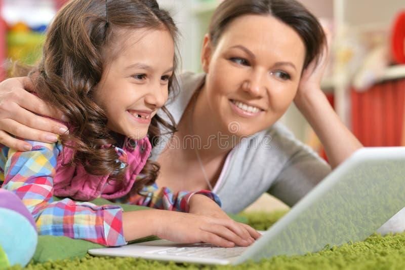 Ritratto della madre e della figlia felici che per mezzo del computer portatile immagini stock libere da diritti
