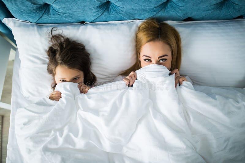 Ritratto della madre e della figlia sotto il piumino insieme alla luce molle di mattina sul letto di tela bianco Concetto della v immagine stock libera da diritti