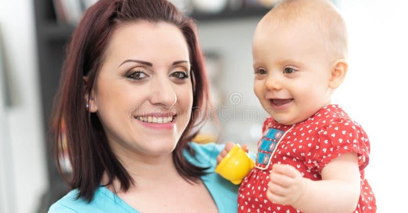 Ritratto della madre felice con la sua neonata sveglia fotografia stock