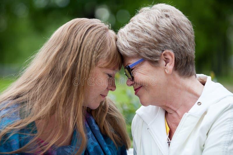 Ritratto della madre sorridente con la figlia che guarda occhio per osservare insieme, all'aperto fotografia stock