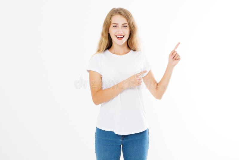 Ritratto della maglietta d'uso sorridente di estate della giovane donna caucasica bionda che indica allo spazio della copia dal d immagine stock