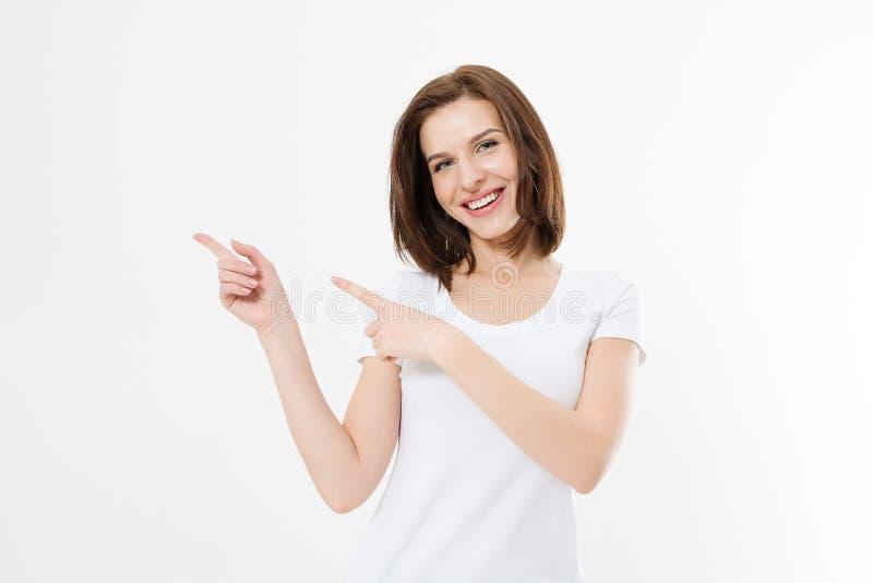 Ritratto della maglietta d'uso sorridente di estate della giovane donna caucasica che indica allo spazio della copia dal dito iso fotografia stock
