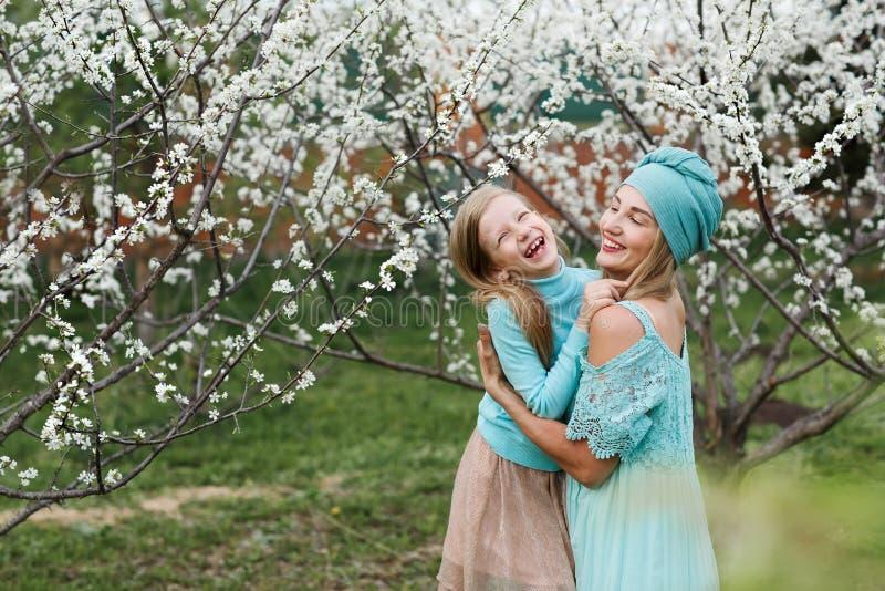 Ritratto della mamma felice con la figlia di risata su un parco della ciliegia della molla Primo piano fotografia stock libera da diritti