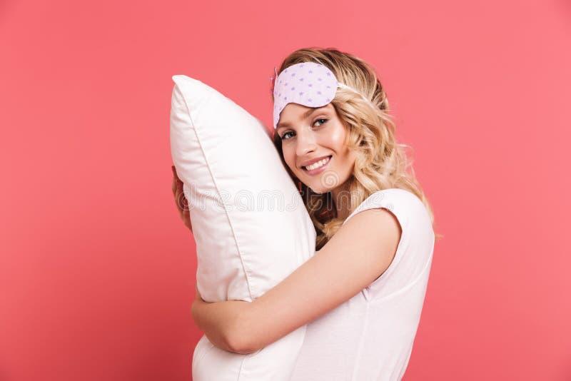 Ritratto della maschera d'uso graziosa di sonno della giovane donna 20s che tiene e che si trova sul cuscino bianco fotografie stock