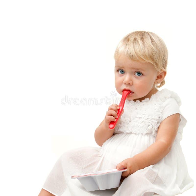 Ritratto della neonata dell'occhio azzurro con il cucchiaio rosso immagini stock