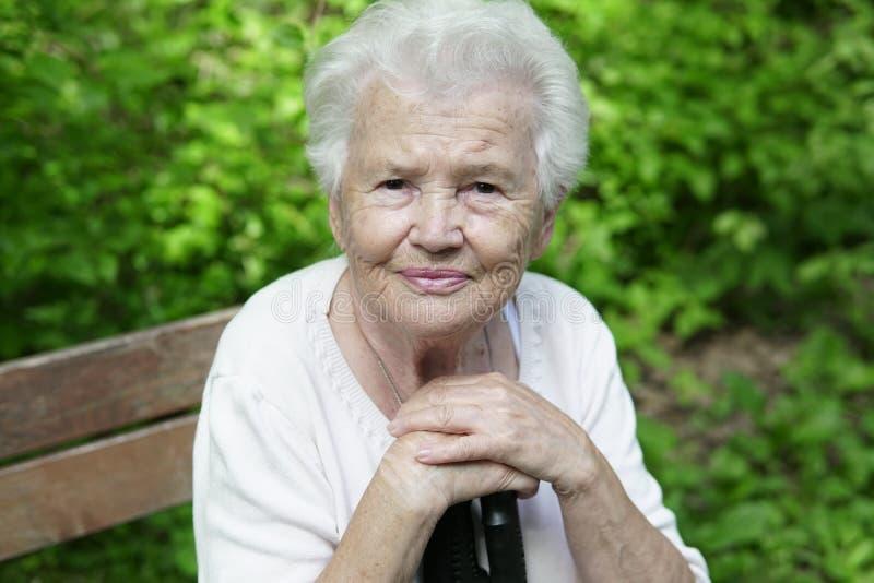 Ritratto della nonna anziana su un banco di parco piacevole immagine stock libera da diritti